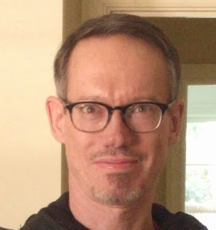 head shot of man with glasses